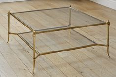 A square patinated brass and glass coffee table. More
