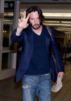 Keanu Reeves flashes the peace sign as he prepares to depart LAX (Los Angeles International Airport).