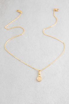 Golden tennis racket charm necklace.