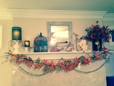 Fall mantle with autumn leaves, candles, birdcage, & acorn garland