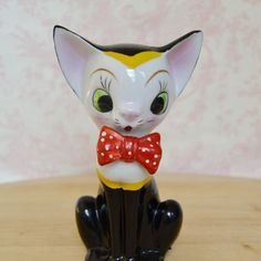This vintage figurine is the cats meow! Made of ceramic with a shiny and matte paint glaze, the cat has large green eyes, black and yellow fur