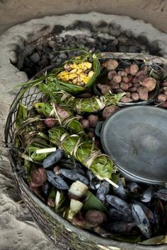 """""""Fish, pork, chicken, breadfruit, potatoes — everything edible is placed in a big basket. Once the basket is packed, it's ready to go into the hole."""" - Zach Stovall, """"ISLANDS Wish List: Cook a Tahitian Feast"""""""