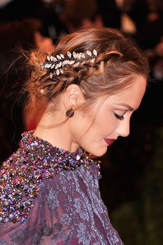 "Minka Kelly: British-meets-punk look that's still romantic and almost gothy.  Kelly's style at the Met Ball For the final touch to this ring of plaits, she deconstructed a necklace into two parts and pinned them on either side of the hair so they laid on top of the braid. ""Pick a necklace that has large chain holes so you can loop a bobby pin into a hole and hold it in place more securely. Crisscross pinning is also key rather than parallel pinning to lock a necklace in place."""