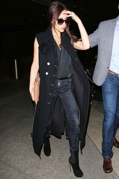 Who: Victoria Beckham What: A Sleeveless Coat Why: The designer is instantly chic in basics paired with a long vest with statement buttons from her new collection. Get the look now: Jenny Kayne coat, $595, revolveclothing.com.   - HarpersBAZAAR.com