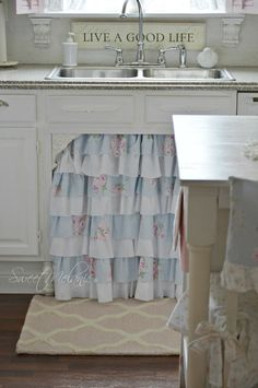 What a cute way to decorate the area in front of the sink!  Love the layers of fabric!