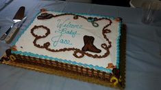 Western theme baby shower cake - Cake baked by Hy-Vee West in Mason City, IA. I just love the extra details they added, especially the little hats and horse shoes on the fence.