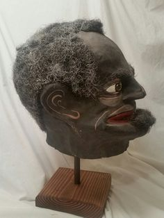 Decorative Arts/Mardi Gras Mask]. An exceedingly rare late 19th century papier-mache Black Minstrel mask, likely for a Mardi Gras parade float. Black matte paint for face, red lips, hair stitched through on head and mustache. Evidence of papier-mache technique inside, tan paper built up in overlapping layers. Opening for eyes, nose and mouth. Exterior paint shows wear, slight crackling & minor abrasions. Approx. 13 in. top to bottom, 10 in. front to back. The Louisiana State Museum h...