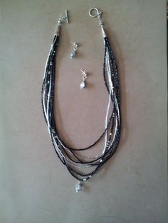 This is a two piece multiple strand necklace with a simple teardrop hanging.