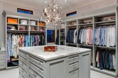 Walk-in closet with open cubbies over clothes rails centered on a gray closet island accented with crystal pulls and a white marble counter illuminated by a modern silver chandelier.