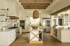 cuisine rustique moderne et blanche aménagée avec un plafond à la française en poutres apparentes, des armoires et des étagères blanches et un bar petit déjeuner en bois et blanc