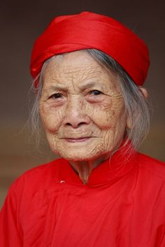 Mrs. Trai (a Noi Due villager) posed for a portrait at the Lim Festival, Bac Ninh, Vietnam, February 26, 2010. The long red dress indicates the woman is at least 90 years old. Photo by Long Pham Thanh.