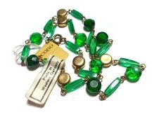 Vintage Coro Choker Green Glass Pegasus 1960s Made in West Germany. Very pretty Coro Necklace with original tags still attached and probably never been worn. Unusual addition of a tag stating that it was made in West Germany for Coro. High quality Coro Pegasus. Green glass beads in two shapes with 5 gold tablet beads spread evenly through. Necklace measures 16 long around. Great addition to a Pegasus Collection.  In excellent vintage condition.