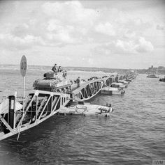 """A Sherman tank of the """"B"""" Squadron 1st Armoured Regiment (10th Armoured Cavalry Brigade 1st Polish Armoured Division) commencing its journey to shore along a floating bridge at Arromanches 26-28 July 1944."""