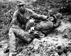 A Chinese soldier tends to a wounded comrade waiting to be transported to a medical dressing station behind the front lines during the Burma Campaign.