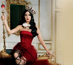 Image of Katy Perry seated on throne next to Killer Queen Fragrance bottle and PINCHme!