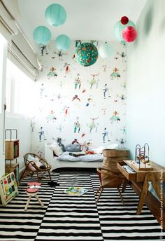 High ceiling playroom with an overhead cloud of paper lanterns, whimsical wallpaper, sleigh bed, box shelves, monochrome striped carpet and midcentury modern wooden chair and desk. Plus a huge sack for corralling toys.