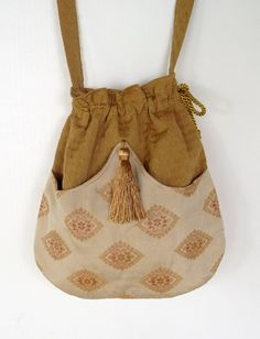 Perfect bag for the free spirited lady. It has the richness of the jacquard in cream with gold diamonds. A gold tassel at the arch pulls it all