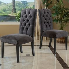 Entertain in style with this set of two grey upholstered dining chairs. Featuring hardwood frames finished with a lovely espresso stain, these chairs are built for durability. Tufted fabric upholstery adds an elegant touch to this set.