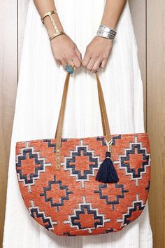 Embroidered tribal-printed, coral & navy bucket tote with a fun tassel and leather shoulder straps