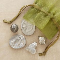 "POCKET CHARMS -- The card enclosed with these rustic pewter pocket charms reads, ""A heart for love; a peace sign for hope; an acorn for a long and healthy life; an angel to watch over you; the world, because its future is in your hands."" Five tokens in a drawstring pouch. Made in USA. Largest is approx. 1""L."
