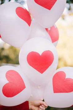 Use Mod Podge and a foam brush to attach tissue paper hearts to helium balloons. Tie on red and white baker's twine.