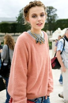 frida gustavsson in an oversized peachy mohair sweater showing the collar of a grey thermal, light wash ripped denim, braided hair and a statement necklace