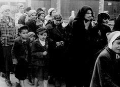 Jewish women and children forced to walk towards the gas chambers. On the platform, some railroad cars are still waiting.