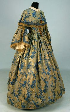 c. 1855 CHANGEABLE SILK BROCADE GOWN. 1-piece grey with blue and platinum floral, boned bodice having pleated open bell sleeve and capelet decorated with fringed ribbon and self piping, lace under-sleeves and collar, full skirt with front pleats and back gauged gathers, brown linen bodice lining, pocket and hem backing. B-34, W-24, L-57.