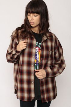 """Vintage 70s shirt by Pendleton in brown, red and beige wool plaid. Buttons up the front with long sleeves.  Every item we sell is authentic vintage and one-of-a-kind! You will receive the EXACT item shown in the photos. For reference, model is 5'9"""" and measures 34-24-35. DETAILS  Best fits: marked large (Note: We only have ONE in stock. If more than one size is listed it is because this item will work on a range of sizes. Check measurements for exact fit.) Condition: very good vintage with…"""