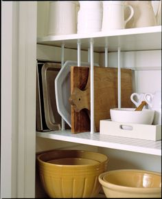Use tension rods to store your cutting boards and baking sheets so they're easily accessible. | 16 Smart Dollar Store Ideas To Organize Your Kitchen