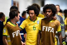Marcelo (C) of Brazil speaks to his teammates Willian (R) and Bernard (L) in the tunnel at the half time during the 2014 FIFA World Cup Brazil Group A match between Cameroon and Brazil at Estadio Nacional on June 23, 2014 in Brasilia, Brazil. (Photo by Jeff Mitchell - FIFA/FIFA via Getty Images)