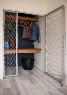 小物もひっかけられるメッシュの扉に。 ポイントは、床の延長・一体感 押入スペースの奥まで手前のフローリング が延長して貼られています。これがけっこう肝でして、これにより、モノをいれて、カーテンなどをかけるにしても、空間に広がりが感じられるのです。マンションのリビング横の和室の改造時など、フローリングを張り替えるタイミングで同時に工事するのをオススメします。 扉をシンプルでフラットな引戸に替え、 中はハンガーパイプだけ付けたいというニーズもあるでしょう。その場合は、どうせ見えない部分なので内部はあえて塗装せずそのままでいいかと思われます。
