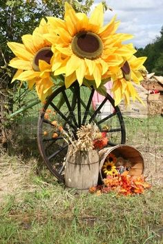 Recreation of a rural harvest scene with large sunflowers wagon wheel and straw basket Stock Photo