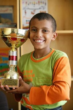 Abdullah, 11, wearing his team's football jersey, smiles as he displays the trophy he won at the 'Safe Children Centre', a UNICEF-supported residence for vulnerable children in the southern port city of Aden, Yeman. Most of the boys who live at the centre formerly lived or worked on the streets, having migrated to the city from the countryside to seek work or escape violence at home.   © UNICEF/Giacomo Pirozzi  http://www.unicef.org
