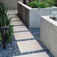 snake plants, blue stones, white pavers, raised beds