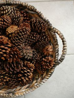 A large basket filled with pinecones makes for simple winter decor - Just add in small glass ornaments for Holiday!  Click photo to see more IDEAS FOR DECORATING WITH PINE CONES - Lynda Quintero-Davids #HomeGoodsHappy -#sponsored