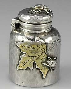 A rare sterling silver inkwell by Tiffany and Company with hammered surface and applied gold washed maple leaves. The cap is lined with cork and unscrews to open back on a hinge. There are four bugs applied to the body. A large bug on the lid and two smaller bugs on the sides. There is also a small bug on a leaf. Dated July 31st 1882. Lined with a glass liner.