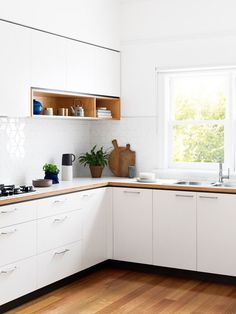 Modern all-white kitchen with wood accents and flower-inspired tile backsplash.
