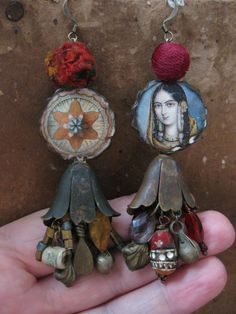 A pair of asymmetrical ceramic decal beads created by etsys Josephine Beads are connected to a set of oxidized brass lily flower pods that dangle a hank of kuchi tribal metal drops, a hand painted terracotta bead, miniature ceramic cup charm, crystal lavender briolettes, gold, periwinkle and vintage crimson seed beads. Earrings measure approximately 4 inches (including length of ear wire).  Mistress of Spices - Each spice has a special day to it. For turmeric it is Sunday, when light drips…