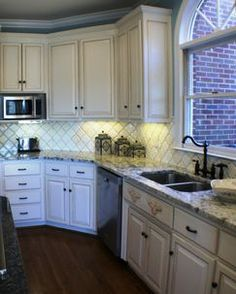 This kitchen got an update with paint and glaze over the existing cabinets. The beveled arabesque backsplash tiles and white ice granite on the perimeter along with a expansive island covered in blue pearl granite make this space a joy for this home cook to use.