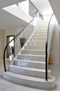 Modern contemporary staircase with curved glass balustrades - constructed from steel, glass, marble and hardwood american walnut handrail.