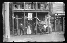 """Through the Lens of Time: Images of African Americans from the Cook Collection - part of VCU Libraries' Digital Collections. This image is labeled """"Emancipation Day, 1888 -- East Main Street near 21st Southside."""" It shows a Richmond storefront decorated for Emancipation Day. A banner with President Lincoln's image is on display. The exact date for the celebration in 1888 in Richmond is not known"""