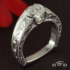 Custom 950 Platinum mounting to hold a partial bezel set 0.80ct round brilliant cut center diamond in 'U' shaped head. Leaf and scroll pattern engraving down shoulders. Curling filigree inset into triangular side face panels.