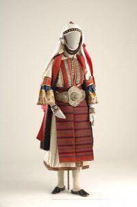 Γυναικεία ενδυμασία Ασβεστοχωρίου - Μακεδονία Η ενδυμασία που ονομάζεται παϊζάνικα, αποτελεί τη νυφική και γιορτινή ενδυμασία των Παϊζάνων (παλαιών κατοίκων του Ασβεστοχωρίου). Τα περισσότερα εξαρτή- ματα της λειτουργούν ως κώδικεςσυνεννόησης και υποδηλώνουν την ηλικία και την κοινωνική κατάσταση της γυναίκας (κοπέλα, νύφη, ηλικιωμένη κ.ά.). Αποτελείται από το υπόλευκο πουκάμισο, το σαγιά, την καπούτα, είδος επενδύτη και την υφαντή ποδιά, τη φούτα. Τη μέση σφίγγει η ζώνη με την πόρπη, το… White Wedding Dresses, Bridal Dresses, White Satin Dress, Bridal Shirts, Greek Culture, Alexander The Great, Folk Costume, Greek Costumes, Manticore