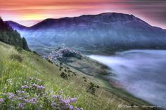 Mount Sibillini, Umbria, Italy | Landscape of Castelluccio di Norcia with the colors of dawn on the Sibillini Mountains and fog on the great plain.