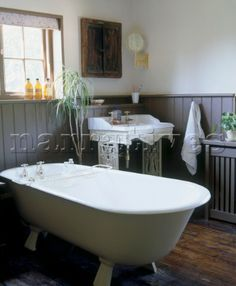 Country style bathroom with a claw foot bathtub ornate sink wood panelling and wood floor