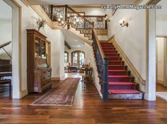 Exquisite estate home with elegant features such as hardwood floors, detailed custom iron railing attached to a grand staircase that opens to the formal living room and dining room. #decorating #ideas #decor #stairs #red #interior #design