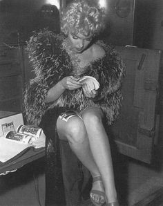 """Marilyn Monroe looking through photos of herself on set of """"The Seven Year Itch.""""  [1954]"""