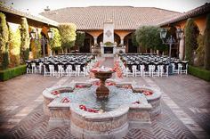 Outdoor fall wedding in courtyard with orange and red flower petals in the fountain and up the aisles | Leslie Ann Photography | villasiena.cc