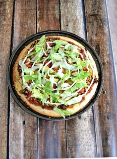 Delicious Taco Pizza starts with Sabra Salsa then is piled high with refried beans, seasoned ground beef, cheese, lettuce, and other toppings.
